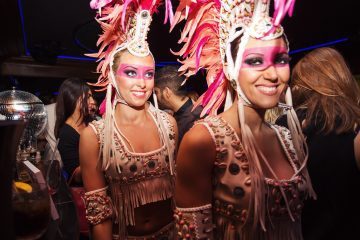 Two women in face paint and carnival costumes